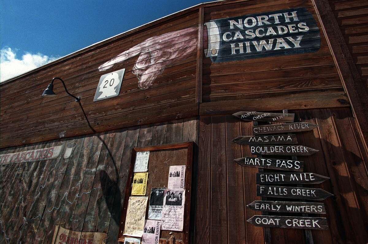 This sign on one of downtown Winthrop's distinctive ersatz western buildings points the way to Hwy 20, the road through the North Cascades, and the signposts below right list some of the classic destinations in the area.