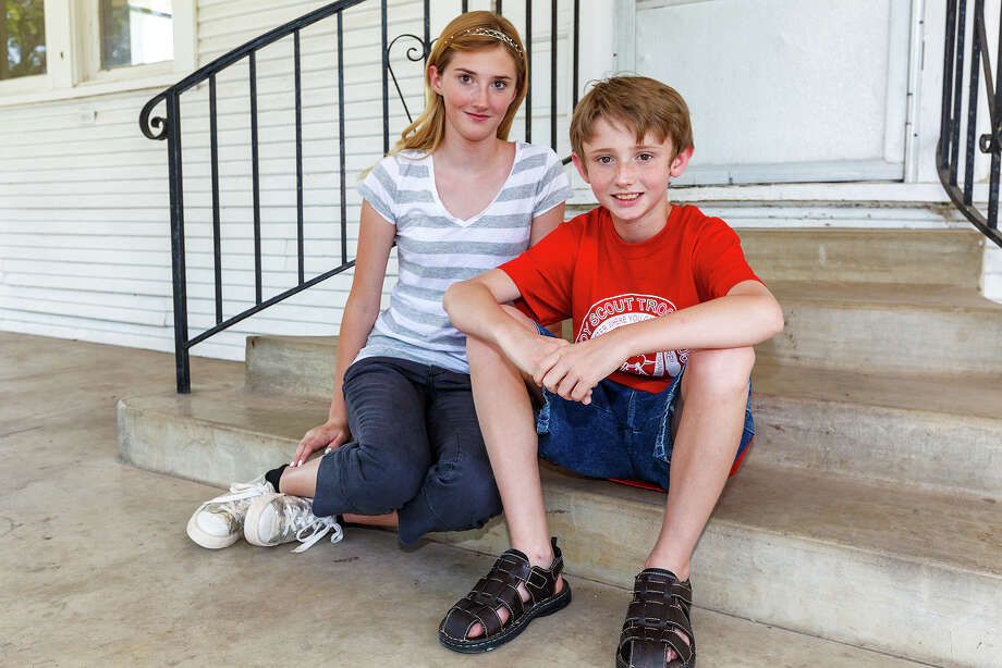 "Eleven-year-old Garrett Overton and his thirteen-year-old sister Catilin in front of the McGimsey house at McGimsey Scout Park, 2226 N.W. Military Highway on June 6, 2012.  Garrett saved his sister's life on Aug. 21, 2011, when he went back into his family's burning house and pulled Caitlin outside to safety.  He has since been awarded the meritorius service award by the Alamo Area Council, Boy Scouts of America and the Honor Medal, ""for unusual heroism in saving or attempting to save life at considerable risk to self"" from the national office for recognition of his bravery. Photo: MARVIN PFEIFFER, Marvin Pfeiffer/ Express-News / Express-News 2012"