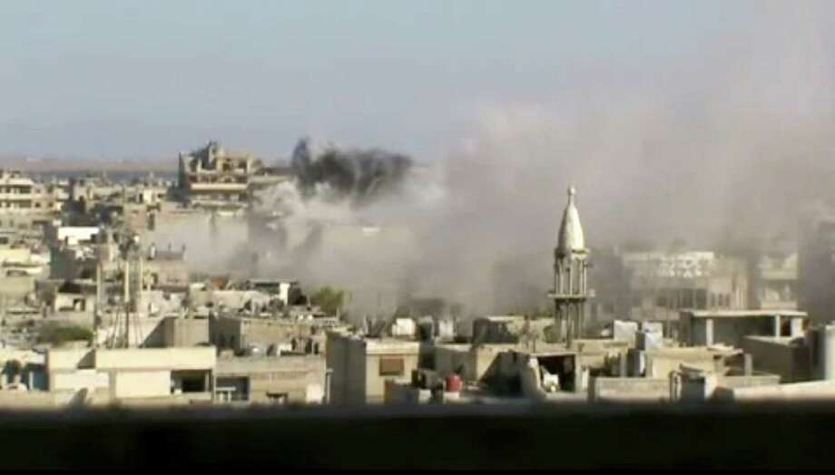 This image made from amateur video released by Shaam News Network and accessed Friday, June 8, 2012, purports to show explosions in the Khaldiyeh area of Homs, Syria. Syrian troops on Friday heavily shelled a rebel-held neighborhood in the flashpoint central city of Homs as President Bashar Assad's troops appeared to be readying to storm the area that has been out of government control for months and it was not clear if U.N. observers were able to enter an area where a massacre occurred this week, activists said. (AP Photo/Shaam News Network via AP video)THE ASSOCIATED PRESS CANNOT INDEPENDENTLY VERIFY THE CONTENT, DATE, LOCATION OR AUTHENTICITY OF THIS MATERIAL Photo: Anonymous / Shaam News Network