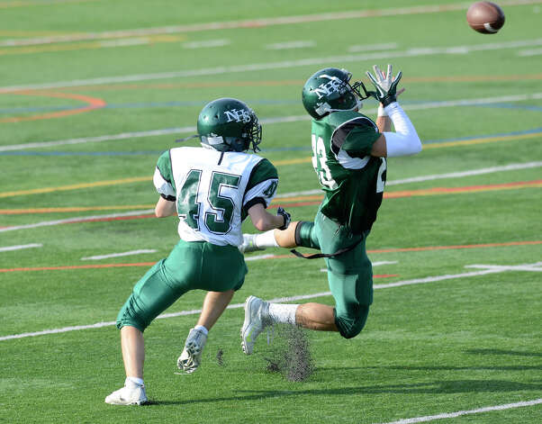 Danny Jakab kicks up some turf as he leaps for a pass near Coltin Larkin as Norwalk High School holds the annual Green and White spring football game at Testa field in Norwalk, CT on Friday June 8, 2012. Photo: Shelley Cryan / Shelley Cryan freelance; Stamford Advocate freelance