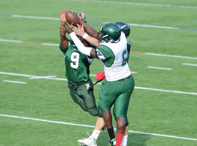 Marc Lerebours (9) and Saeed Soulemane (6) reach for a pass as Norwalk High School holds the annual Green and White spring football game at Testa field in Norwalk, CT on Friday June 8, 2012. Photo: Shelley Cryan / Shelley Cryan freelance; Stamford Advocate freelance