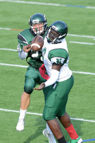 Saeed Soulemane (6) and #23 reach for a pass as Norwalk High School holds the annual Green and White spring football game at Testa field in Norwalk, CT on Friday June 8, 2012. Photo: Shelley Cryan / Shelley Cryan freelance; Stamford Advocate freelance