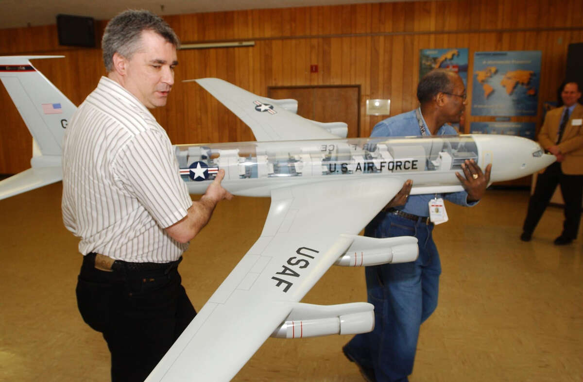 Bill Balint, left, and Harry Penn, of the defense contractor Norden Systems in Norwalk, carry a model of the JointStars 707 Air Force surveillance plane to show U.S. Sen. Chris Dodd how the company;s radar is used. Dodd was a frequent visitor to the plant, which parent Northrop Grumman says it will close at the end of 2013. File photo.