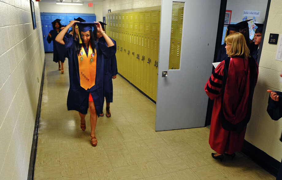 Graduate Jerelyn Figueroa fixes her cap as she makes her way with her classmates to the gym, during Notre Dame of Fairfield's Class of 2012 Commencement Exercises in Fairfield, Conn. on Friday June 8, 2012. Photo: Christian Abraham / Connecticut Post