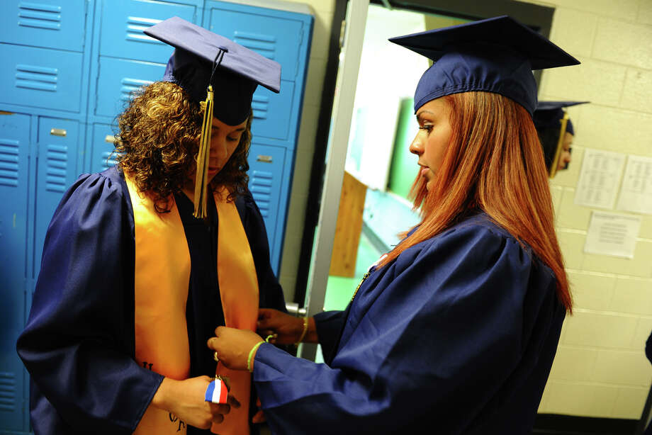Corinna Santos, of Trumbull, right, helps Bianka Bell, of Shelton, with her sash, during Notre Dame of Fairfield's Class of 2012 Commencement Exercises in Fairfield, Conn. on Friday June 8, 2012. Photo: Christian Abraham / Connecticut Post