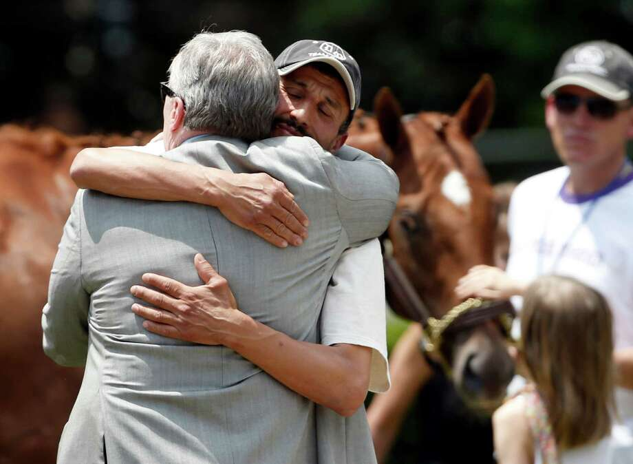 Owner J. Paul Reddam, left, is hugged by groom Incencio Diaz as Kentucky Derby and Preakness winner I'll Have Another is petted in the background after a news conference at Belmont Park in Elmont, N.Y., on Friday, June 8, 2012. I'll Have Another's bid for a Triple Crown ended with the shocking news that the colt was out of the Belmont Stakes due to a swollen left front tendon. The Belmont Stakes horse race is Saturday. Photo: Mike Groll, Associated Press / AP