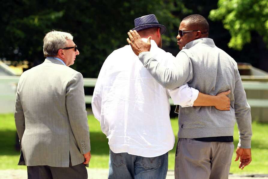 Trainer Doug O'Neil (C) hugs Derrick Mayes as owner J. Paul Reddam looks on after a press conference