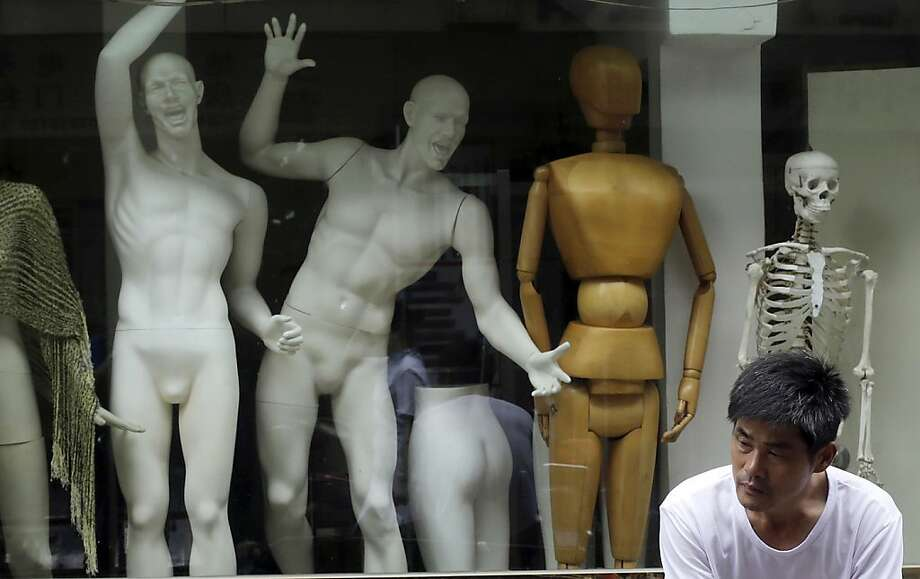 The evolution of the mannequin in Shanghai: From right, skeleton to wooden artist's model to party animal. Photo: Eugene Hoshiko, Associated Press