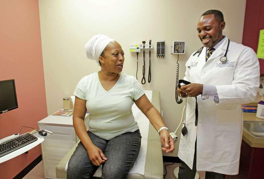 Diane Jackson's blood pressure is one of the things Dr. Kelvin Shepherd monitors when she visits El Centro de Corazón's clinic. Photo: Melissa Phillip / © 2012 Houston Chronicle