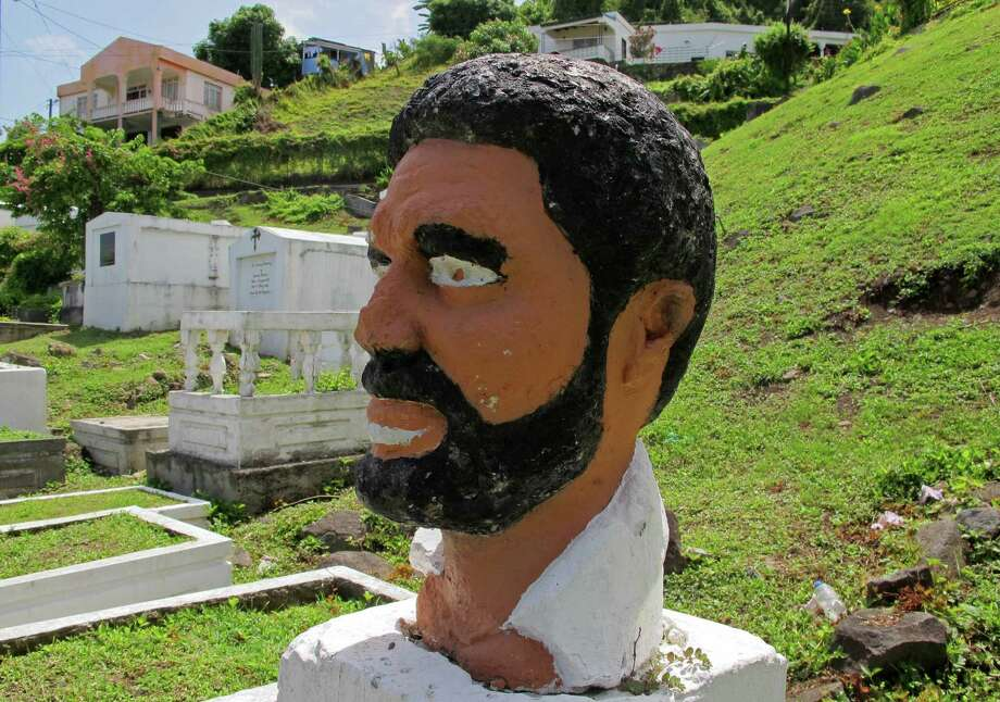 This picture taken Sunday, June 3, 2012, shows a bust of Grenada's former Prime Minister Maurice Bishop standing in a corner of a sprawling hillside cemetery where forensic experts believe the executed leader's body was buried in an unmarked grave in 1983 in St. George's, Grenada. A haunting Cold War mystery is getting a fresh look on the Caribbean island of Grenada, where the body of the Marxist prime minister is still missing nearly 30 years after he was executed during a bloody coup that sparked a U.S. invasion. (AP Photo/David McFadden) Photo: David McFadden / AP