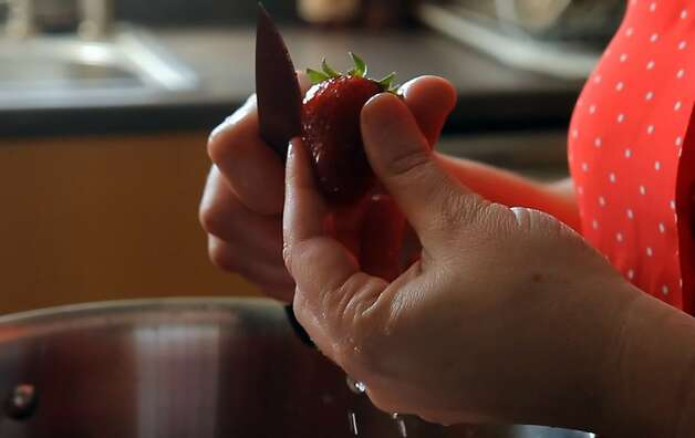 Carolina Braunschweig cuts the stem off a strawberry as she demonstrates how to make strawberry jam in the Chronicle test kitchen on Thursday, May 17, 2012, in San Francisco, Calif. Photo: Carlos Avila Gonzalez, The Chronicle