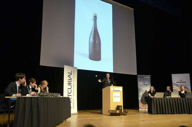 Artcurial's Auctioneer Arnaud Oliveux (C) auctions a bottle of champagne in Mariehamn, aland, on June 8, 2012. A 200-year-old bottle of Veuve Clicquot Ponsardin champagne found on the bottom of the Baltic fetched 15,000 euros (18,600 USD) today in Finland, less than half what sale organisers had hoped. A total of 11 bottles of the world's oldest champagne were sold today for 109,280 euros (136,000 USD), two years after being salvaged from the sea off  Finland's autonomous island province of Aaland. Photo: Erkki Santamala, AFP/Getty Images