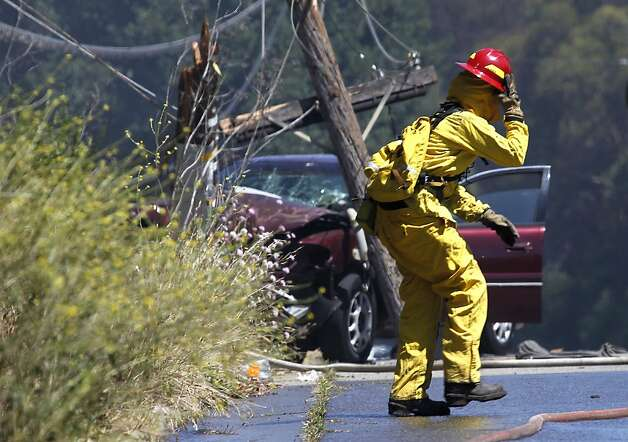 An Oakland firefighter moves past the scene of an accident which caused a brush fire on a steep hill after the car broke a power pole near eastbound Interstate 580 in Oakland, Calif. on Friday, June 8, 2012. Photo: Paul Chinn, The Chronicle