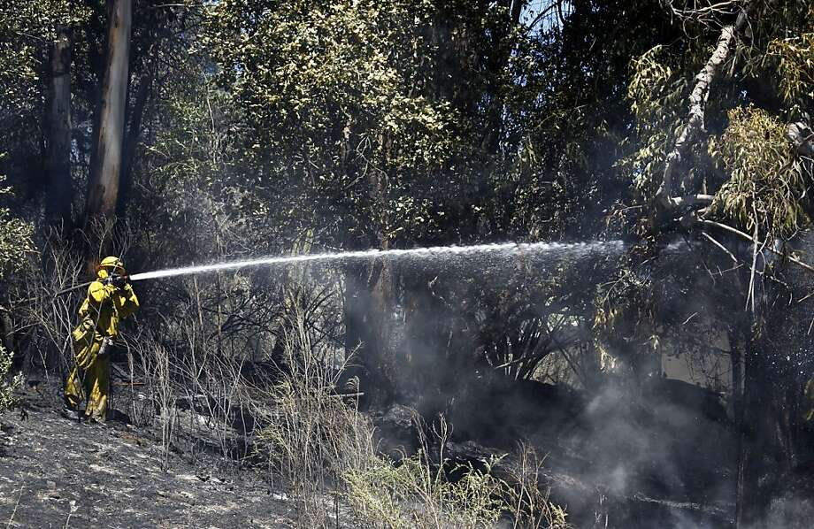 Oakland firefighters extinguish a brush fire on a steep hill near eastbound Interstate 580 in Oakland, Calif. on Friday, June 8, 2012 after a car crashed into a power pole on Mountain Boulevard which ignited the dry hillside. Photo: Paul Chinn, The Chronicle