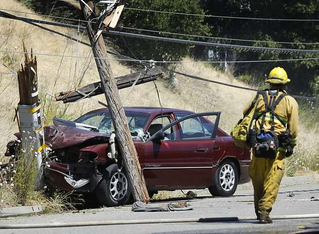 An Oakland firefighter views the scene of an accident which caused a brush fire on a steep hill after the car broke a power pole near eastbound Interstate 580 in Oakland, Calif. on Friday, June 8, 2012. Photo: Paul Chinn, The Chronicle