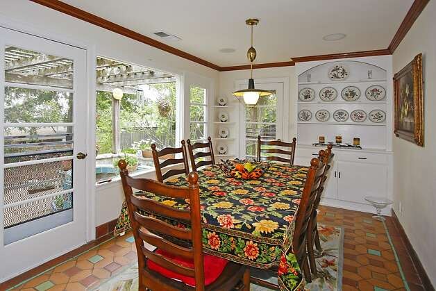 A kitchen nook with a hutch features tile flooring, decorative and recessed lighting, and a wall of windows overlooking the patio and fenced backyard. Photo: Terrace Associates