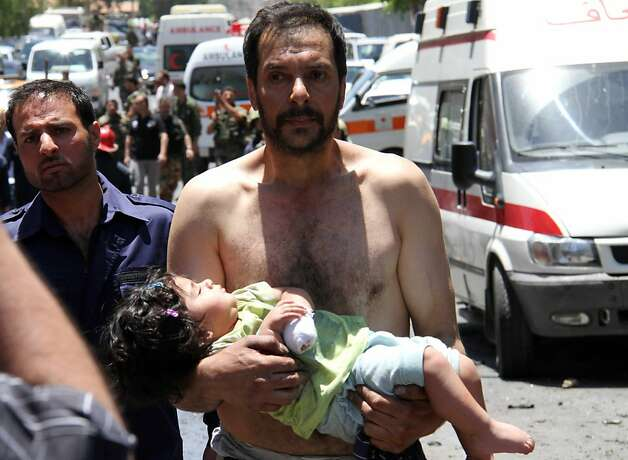 TOPSHOTS A Syrian man carries a wounded girl next to Red Crescent ambulances following an explosion that targeted a military bus near Qudssaya, a neighbourhood of the Syrian capital, on June 8,  2012. At least seven people were killed in blasts near Damascus and in Idlib city in Syria's restive northwest, among them four security forces members, a watchdog said.   AFP PHOTO/STR-/AFP/GettyImages Photo: -, AFP/Getty Images