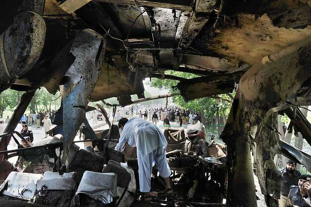 TOPSHOTS Pakistani security officials examine the wreckage of a destroyed bus after a bomb explosion on the outskirts of Peshawar on June 8, 2012. A bomb blast ripped through a Pakistani bus on June 8, killing at least 18 people, including six women and a child, on the outskirts of Pakistan's northwestern city of Peshawar, police said. More than 40 other people were wounded in the attack on a bus rented by the government to take staff home after work in the northwestern province of Khyber Pakhtunkhwa. AFP PHOTO / A. MAJEEDA. MAJEED/AFP/GettyImages Photo: A. Majeed, AFP/Getty Images