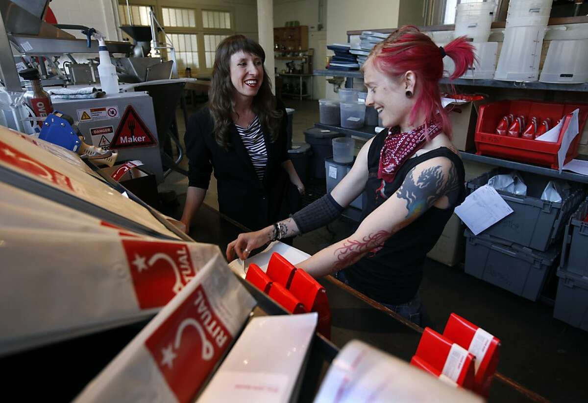 Eileen Hassi (left), owner of Ritual Coffee Roasters, talks with employee Kaleena Stoddard at the company's roastery in San Francisco, Calif. on Thursday, June 7, 2012.