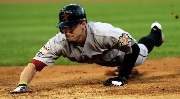 Houston Astros' Jordan Schafer dives safely back to first base during a pickoff-attempt by the Chicago White Sox in the third inning of a baseball game on Friday, June 8, 2012, in Chicago. Photo: AP