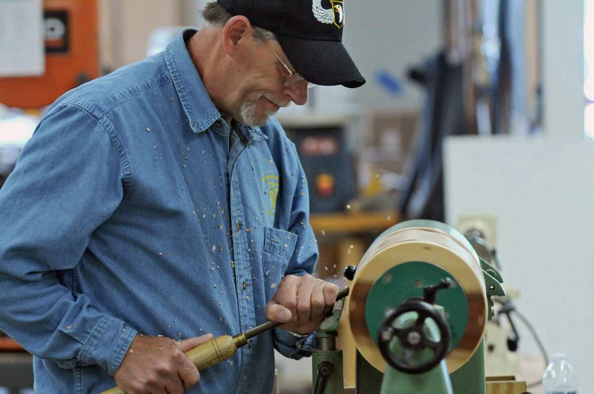 Kurt Roullier of Wynantskill, an Army veteran who was a member of the 101st Airborne Division from 1974-77, uses a lathe to smooth the rounded sides of an urn at the Northeastern Woodworkers Association, where he and other volunteer woodworkers are making wooden urns for interment of unclaimed remains of veterans, on Thursday June 7, 2012 in Cohoes, NY. (Philip Kamrass / Times Union )
