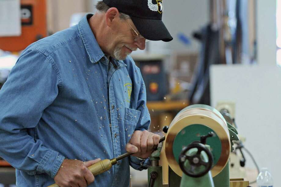 Kurt Roullier of Wynantskill, an Army veteran who was a member of the 101st Airborne Division from 1974-77,  uses a lathe to smooth the rounded sides of an urn at the Northeastern Woodworkers Association, where he and other volunteer woodworkers are making wooden urns for interment of unclaimed remains of veterans,  on Thursday June 7, 2012 in Cohoes, NY. (Philip Kamrass / Times Union ) Photo: Philip Kamrass