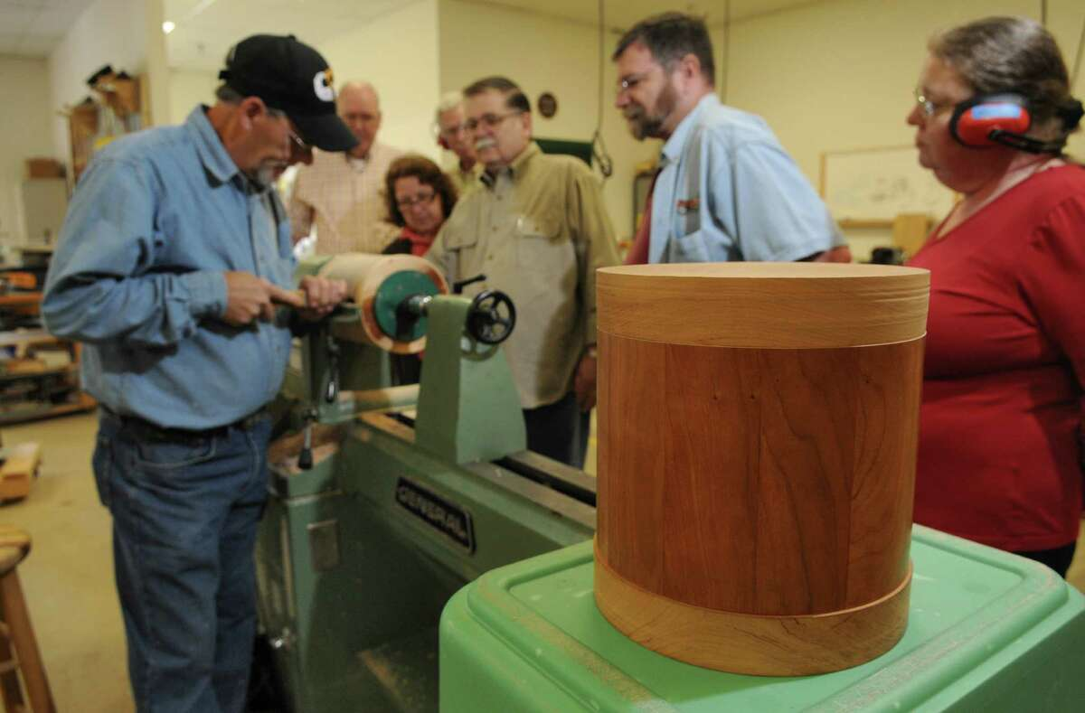 Kurt Roullier of Wynantskill, an Army veteran who was a member of the 101st Airborne Division from 1974-77, uses a lathe to smooth the rounded sides of an urn at the Northeastern Woodworkers Association, where he and other volunteer woodworkers are making wooden urns for interment of unclaimed remains of veterans, on Thursday June 7, 2012 in Cohoes, NY. A finished urn is at right. (Philip Kamrass / Times Union )