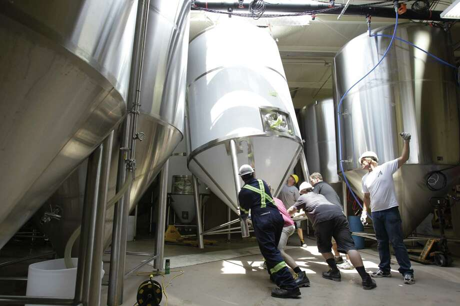 Workers position a new 90-barrel fermenting tank, which can cost about $45,000, at Karbach Brewing Co.  The 9-month-old company is already expanding as the craft-beer boom in Houston keeps building. Photo: Melissa Phillip / © 2012 Houston Chronicle