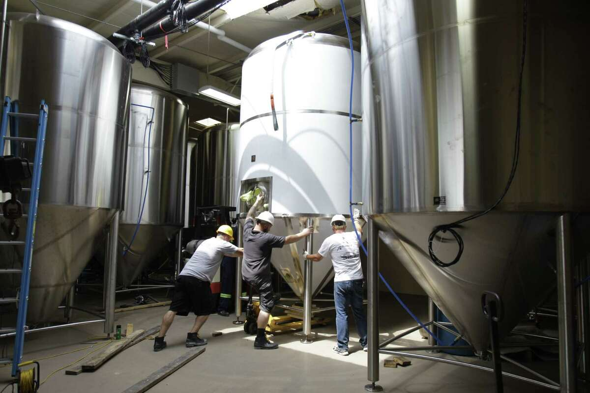 Workers position a new 90 barrel fermenting tank at Karbach Brewing Co., 2032 Karbach St., Thursday, June 7, 2012, in Houston. ( Melissa Phillip / Houston Chronicle )