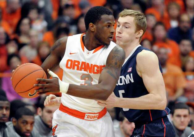 Syracuse's Dion Waiters, left, drives against Connecticut's Niels Giffey during the first half of an NCAA college basketball game in Syracuse, N.Y., Saturday, Feb. 11, 2012. (AP Photo/KevinRivoli) Photo: Kevin Rivoli, Associated Press / FR60349 AP