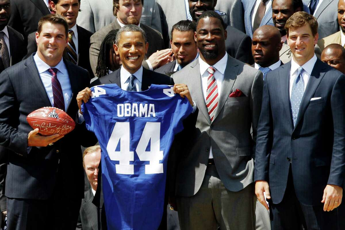 President Barack Obama poses with New York football Giants captains, from left: Zak DeOssie; Justin Tuck; Eli Manning, on the South Lawn at the White House in Washington, Friday, June 8, 2012, during a ceremony where the president honored the Super Bowl XLVI champions New York Giants. (AP Photo/Charles Dharapak)