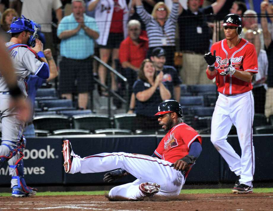 Atlanta's Jason Heyward slides across the plate with the winning run in the 10th inning of the Braves' 4-3 victory over Toronto, their fifth consecutive win. Photo: Hyosub Shin / Atlanta Journal-Constitution