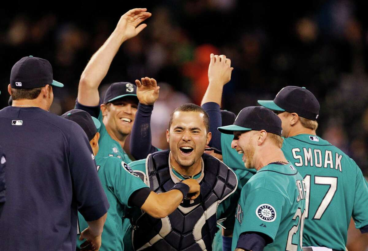 Seattle Mariners catcher Jesus Montero, center, celebrates with teammates, including closer Tom Wilhelmsen, left, after the final out against the Los Angeles Dodgers in a baseball game Friday, June 8, 2012, in Seattle. The Mariners won 1-0 in a six-pitcher combined no-hitter.