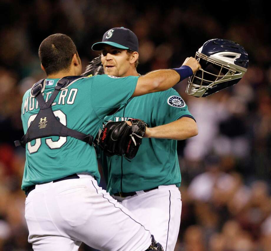 Seattle Mariners catcher Jesus Montero, left, leaps into the arms of closer Tom Wilhelmsen after the final out against the Los Angeles Dodgers in a baseball game Friday, June 8, 2012, in Seattle. The Mariners won 1-0 in a six-pitcher combined no-hitter. Photo: AP