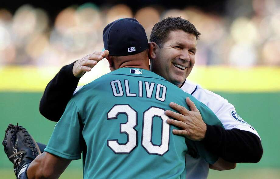 Former Seattle Mariner Edgar Martinez, right, embraces catcher Miguel Olivo after Martinez threw out the ceremonial first pitch before the Mariners' baseball game against the Los Angeles Dodgers on Friday, June 8, 2012, in Seattle. Photo: AP