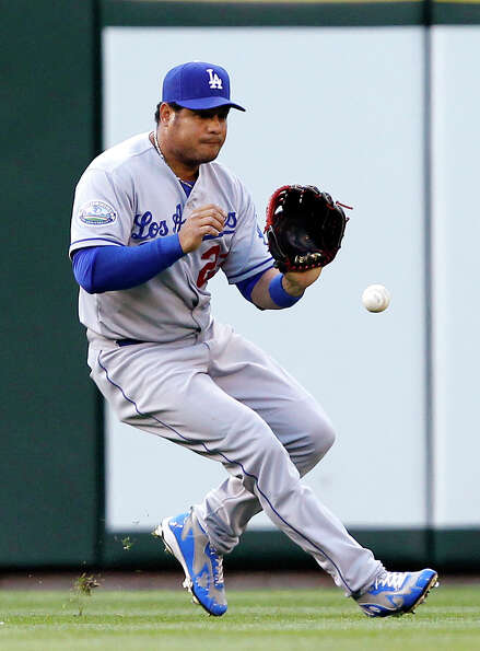 Los Angeles Dodgers left fielder Bobby Abreu fields a single from Seattle Mariners' Ichiro Suzuki in