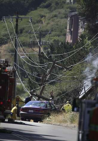 A vehicle that knocked down a power pole and caused a brush fire is seen on Mountain Boulevard as emergency responders work near it on Friday, June 8, 2012 in Oakland, Calif. Photo: Lea Suzuki, The Chronicle