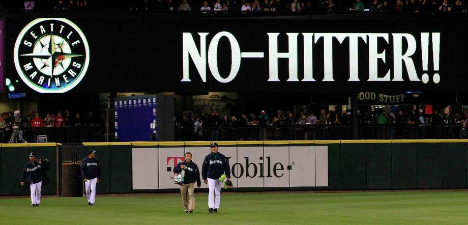 "Seattle Mariners head in from the bullpen as a sign flashes ""No-Hitter!!"" behind after a baseball game against the Los Angeles Dodgers Friday, June 8, 2012, in Seattle. The Mariners won 1-0 in a six-pitcher combined no-hitter. Photo: AP"