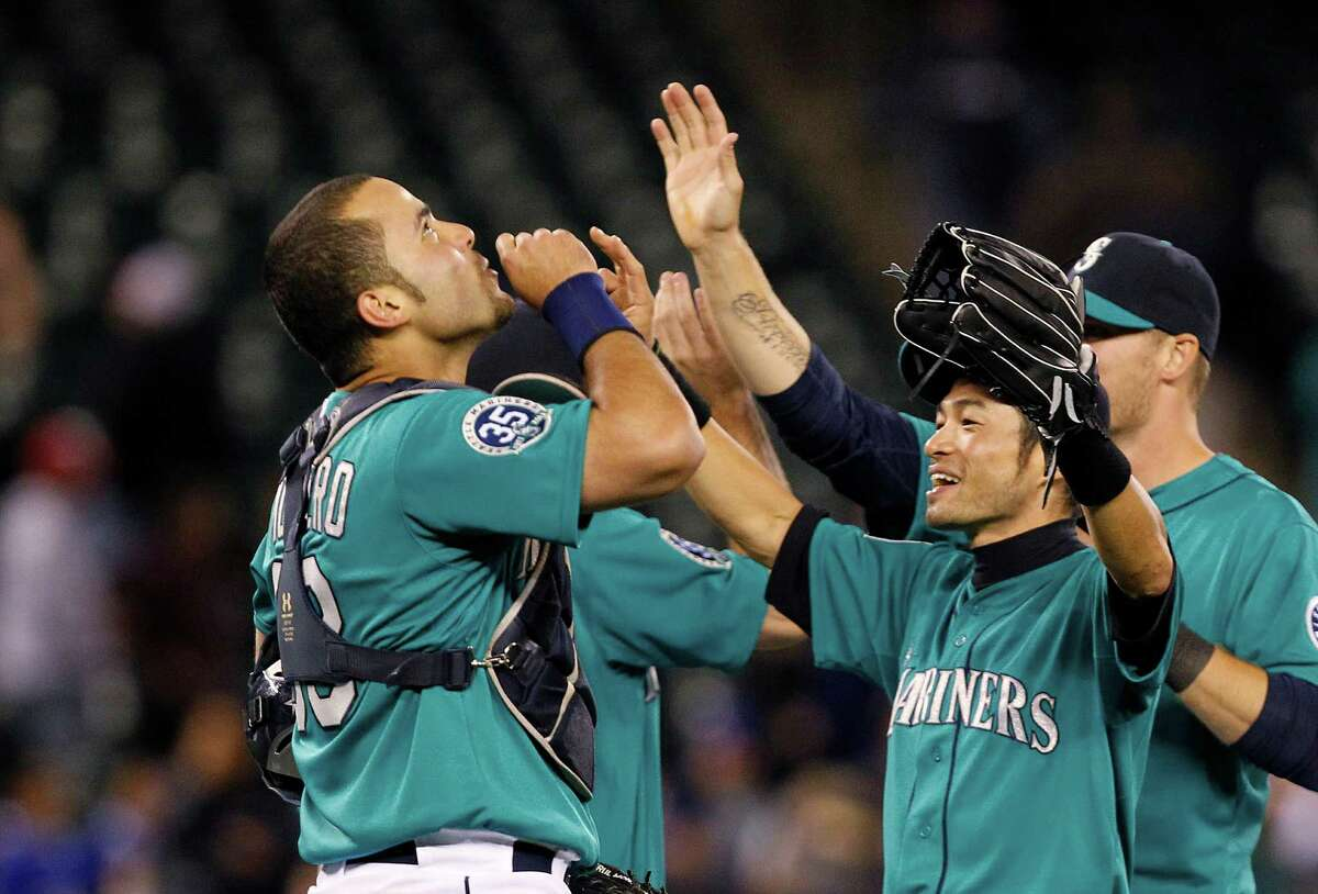 Seattle Mariners catcher Jesus Montero, left, faces skyward as Ichiro Suzuki celebrates after the team beat the Los Angeles Dodgers in a baseball game Friday, June 8, 2012, in Seattle. The Mariners won 1-0 in a six-pitcher combined no-hitter.