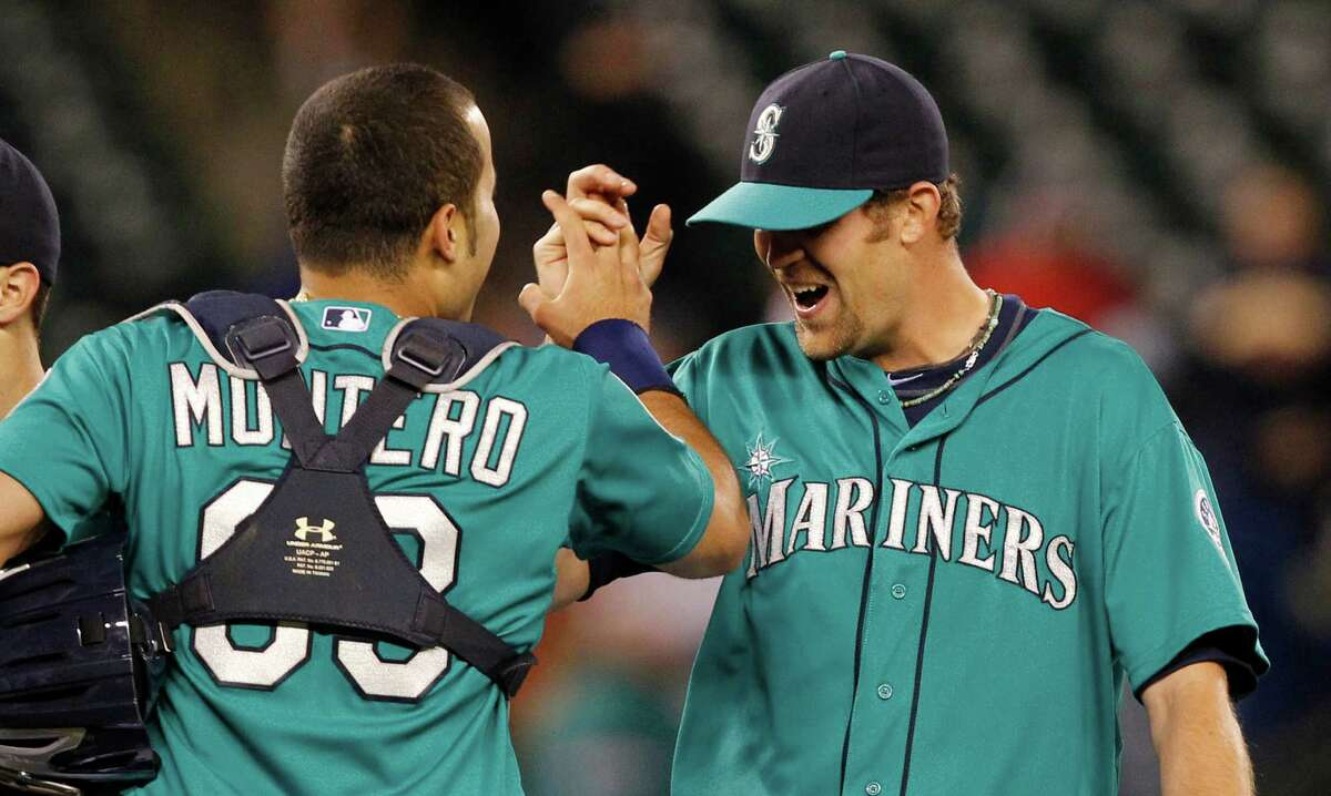 Seattle Mariners catcher Jesus Montero, left, celebrates with closer Tom Wilhelmsen after the final out against the Los Angeles Dodgers in a baseball game Friday, June 8, 2012, in Seattle. The Mariners won 1-0 in a six-pitcher combined no-hitter.