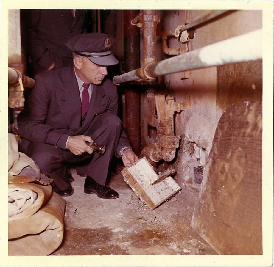 This 1962 photo from the U.S. Penitentiary Alcatraz shows correctional officer Orrin T. Maybee looking over the inside of the escape hole and the cover fashioned by the prisoners. Photo: Handout Photo, U. S. Penitentiary Alcatraz