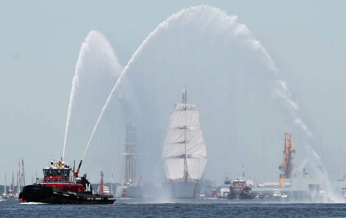 A tug shoots streams of water as a welcome for the Coast Guard tall ship Eagle leads other tall ships and escort vessels in a parade of sail for OpSail 2012 in Norfolk, Va., Friday , June 8,, 2012.