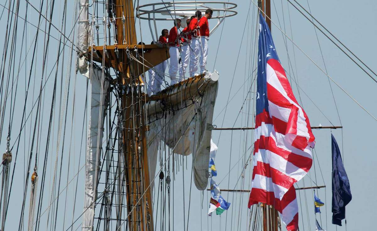 Sailors aboard the Colombian tall ship Gloria man the rigging as they pass an 1812 flag during a parade of sail for OpSail 2012 in Norfolk, Va., Friday , June 8, 2012.