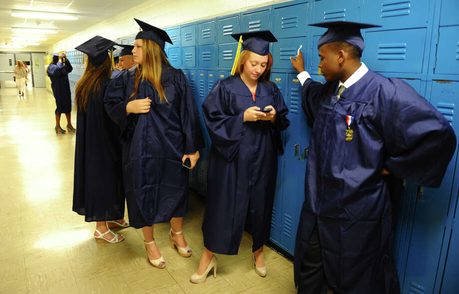 Caitlyn Campodonico does some last minute texting before the start of Notre Dame of Fairfield's Class of 2012 Commencement Exercises in Fairfield, Conn. on Friday June 8, 2012. Photo: Christian Abraham / Connecticut Post