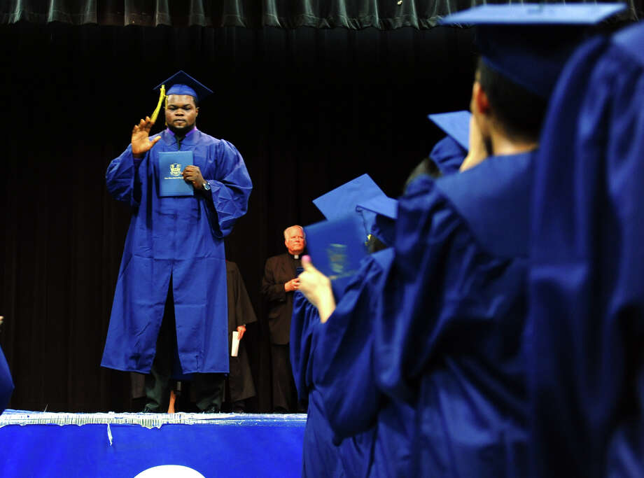 Graduate Theo Tumba acknowledges his classmates as they give him a standing ovation after getting his diploma, during Notre Dame of Fairfield's Class of 2012 Commencement Exercises in Fairfield, Conn. on Friday June 8, 2012. Tumba's father died just two days before graduation. Photo: Christian Abraham / Connecticut Post