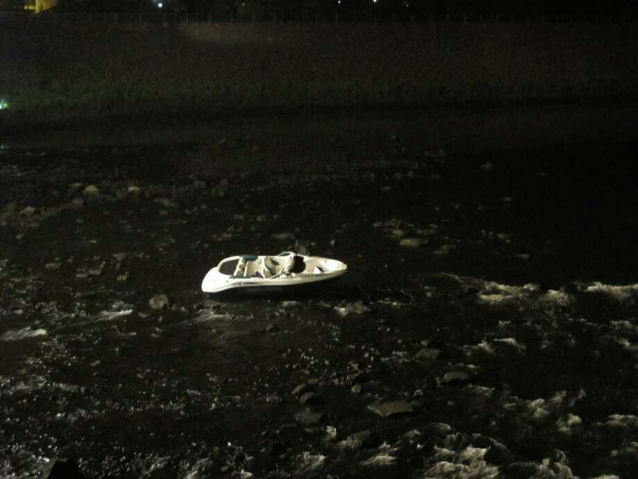 A boat that got loose from its owner and wound up stuck in the Naugatuck River near Main Street caused a scare Friday night. Photo: Tom Cleary / Connecticut Post