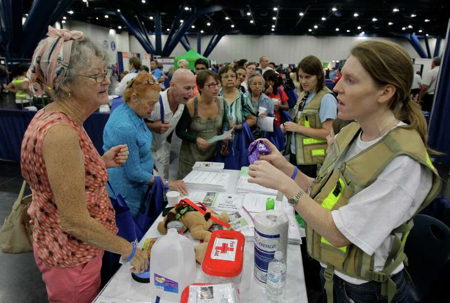 Lucille Wallace, left, of Houston talks with SPCA volunteer, Betsy Dillard, right,  of Houston at the SPCA booth on hurricane pet preparedness during the Houston/Galveston National Weather Service 2012 Hurricane Workshop at the George R Brown Convention Center Saturday, June 9, 2012, in Houston. Photo: Melissa Phillip, Houston Chronicle / © 2012 Houston Chronicle