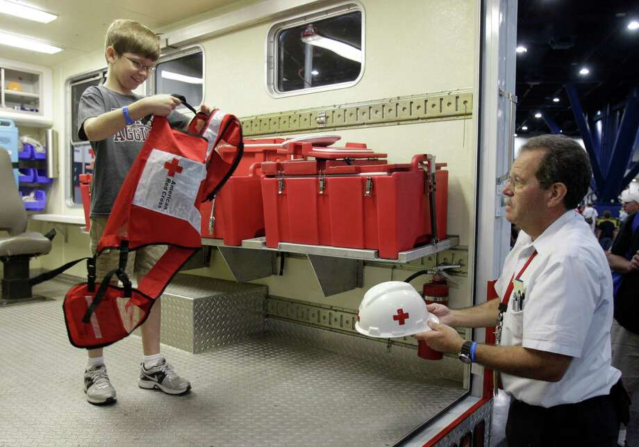 Ryan Williamson, 10, of El Campo is helped by Red Cross volunteer, Mark Zentner, of Houston, to try on a vest and hard hat inside a Red Cross emergency response vehicle during the Houston/Galveston National Weather Service 2012 Hurricane Workshop at the George R Brown Convention Center. Photo: Melissa Phillip, Houston Chronicle / © 2012 Houston Chronicle