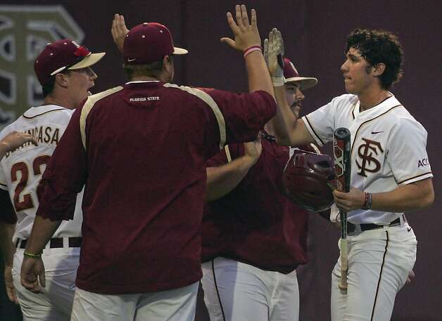 Florida State's Josh Delph, right, celebrates with teammates after scoring in the fourth inning of an NCAA college baseball tournament super regional game against Stanford, Friday, June 8, 2012, in Tallahassee, Fla. (AP Photo/Phil Sears) Photo: Phil Sears, Associated Press