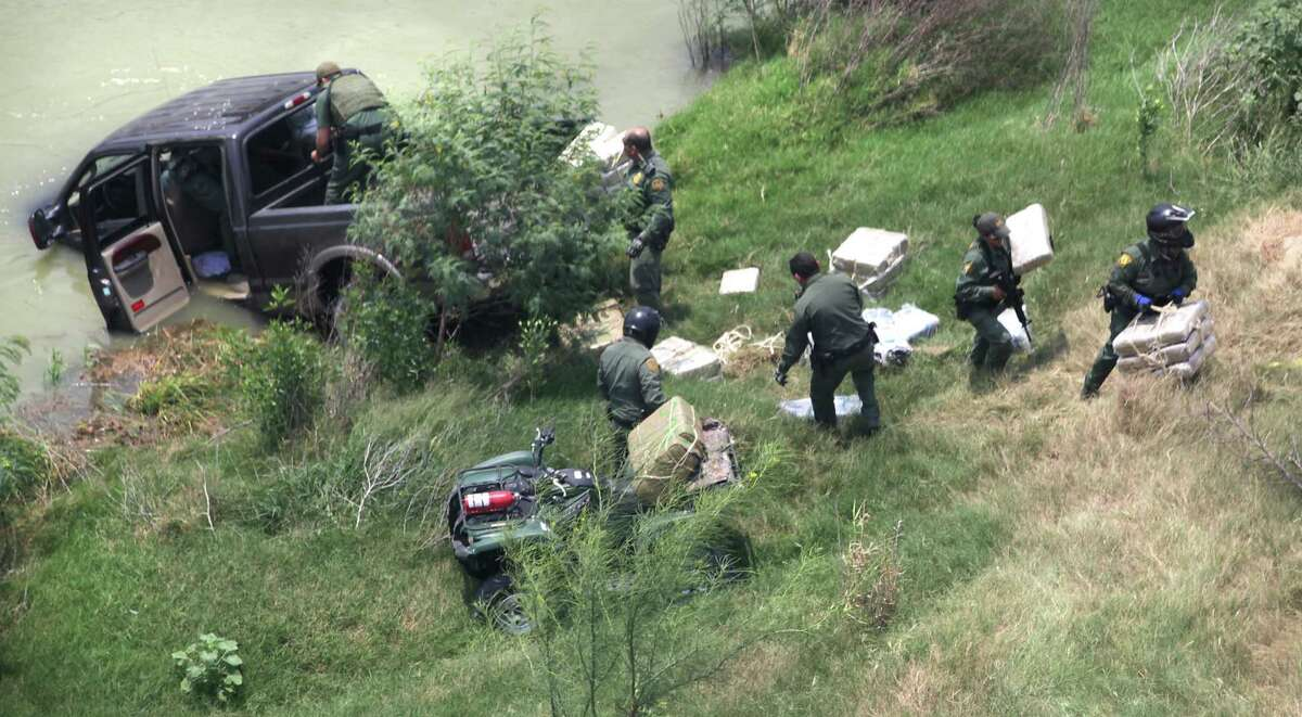 Border agents remove packages of drugs from a stolen pickup truck that had been detected and chased back to the Rio Grande River where the occupants ditched the truck in the river and swam back to Mexico. Thursday, May 3, 2012.